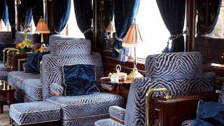 Plush blue-velvet zebra print armchairs lining a train bar car