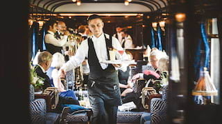 Barman holding cocktails on a tray and stepping through a train bar car