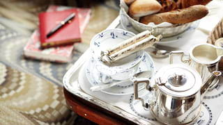 Close-up of a continental breakfast on a silver tray, including silver tea pot