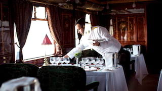 Restaurant steward in a white tux setting tables in a vintage train carriage