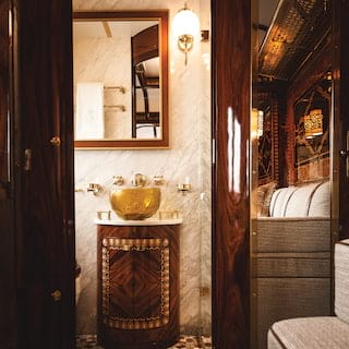 Train cabin bathroom with ornate gold-plated sink and marble-tiled walls