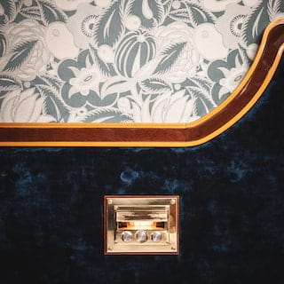 Close-up of a gleaming brass wall light detail on a blue-velvet bed headboard