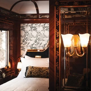 Glamorous train cabin with glass tulip wall lights and a pillowy king-size bed