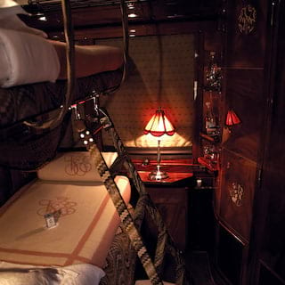 Lamplit twin train cabin with cosy bunk beds and gleaming wood-panelled walls