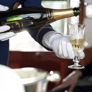 Close-up of white-gloved hands pouring champagne into a champagne flute