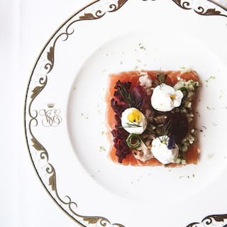 Birds-eye-view of a smoked salmon starter garnished with edible flowers