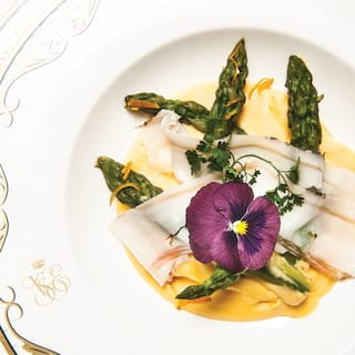 Birds-eye-view of an asparagus dish garnished with edible flowers