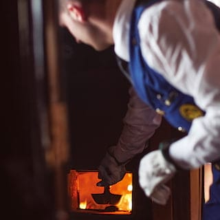 White-gloved train guard shoveling coal into a small hot water furnace