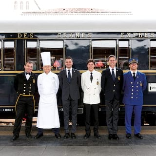 Head Chef, Maître D' and Train Manager and stewards in front of a train carriage