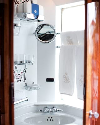 White porcelain sink with silver taps and details in a corner wash cabinet