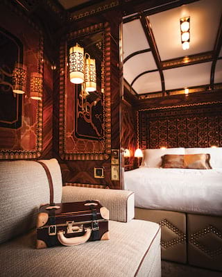 Glamorous train cabin suite with king-size bed, ornate marquetry and plush sofa