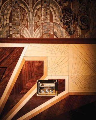 Close-up of ornate art deco marquetry on a gleaming wood-panelled wall