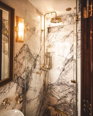 Marble-tiled train cabin ensuite with brass rain shower and Lalique glass light