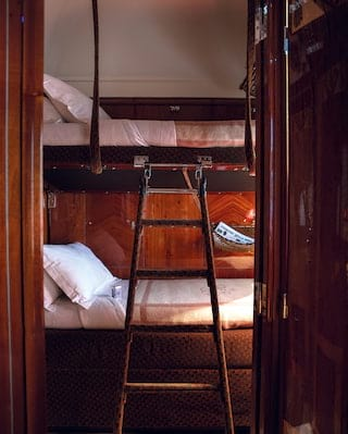 Vintage train bed berth next to a ladder leading to a top bunk