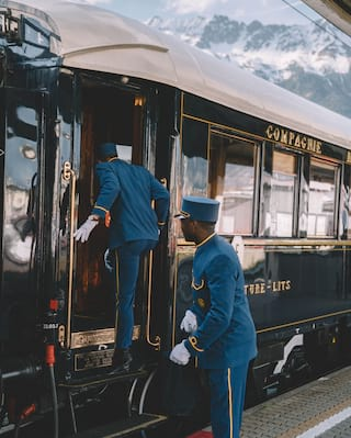 Two blue-uniformed stewards stepping onto a luxury train