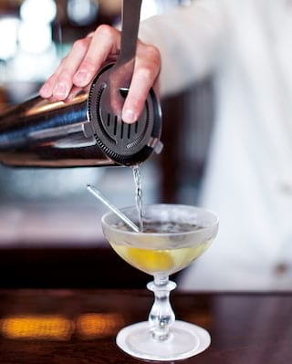 Close-up of a martini cocktail being poured from a shaker into a coupe glass