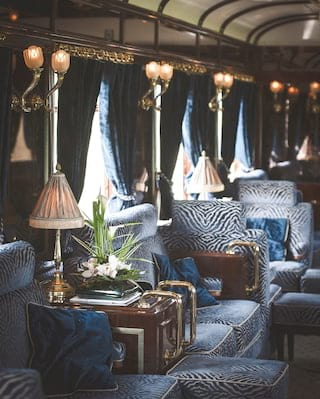 Close-up of a train bar car with blue velvet zebra print seating and brass details