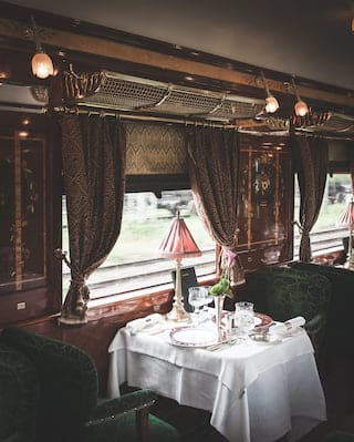 Vintage train dining car with French-polished wood panels and green velvet chairs