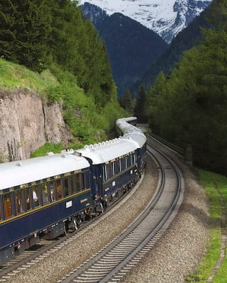 Gleaming blue and gold-detailed carriages snaking through a verdant valley