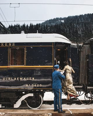 Train steward in a blue uniform helping a lady step up into a blue train carriage