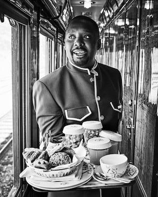 Foto in bianco e nero di un assistente di bordo del treno che attraversa un corridoio stretto di legno