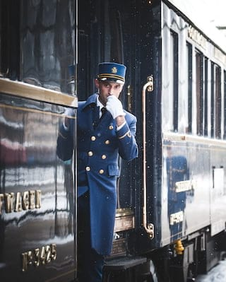 Train guard in a blue uniform blowing a whistle next to train carriages