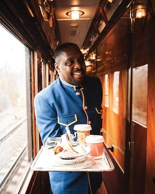 Smiling train steward in a blue uniform holding a continental breakfast tray
